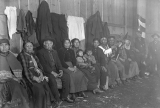Indians seated inside Tulalip smoke house (long house, potlatch house)