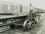 Great Northern Railroad Log Flat Car and worker at Delta Yards in Everett, Washington.