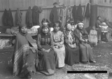 Indian Women seated inside Tulalip Reservation smoke house (long house, potlatch house).