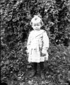 Child standing in front of foliage